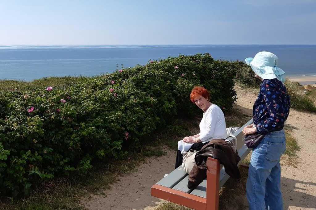 ältere Dame auf einer Bank am Meer, mit Schwiegertochter
