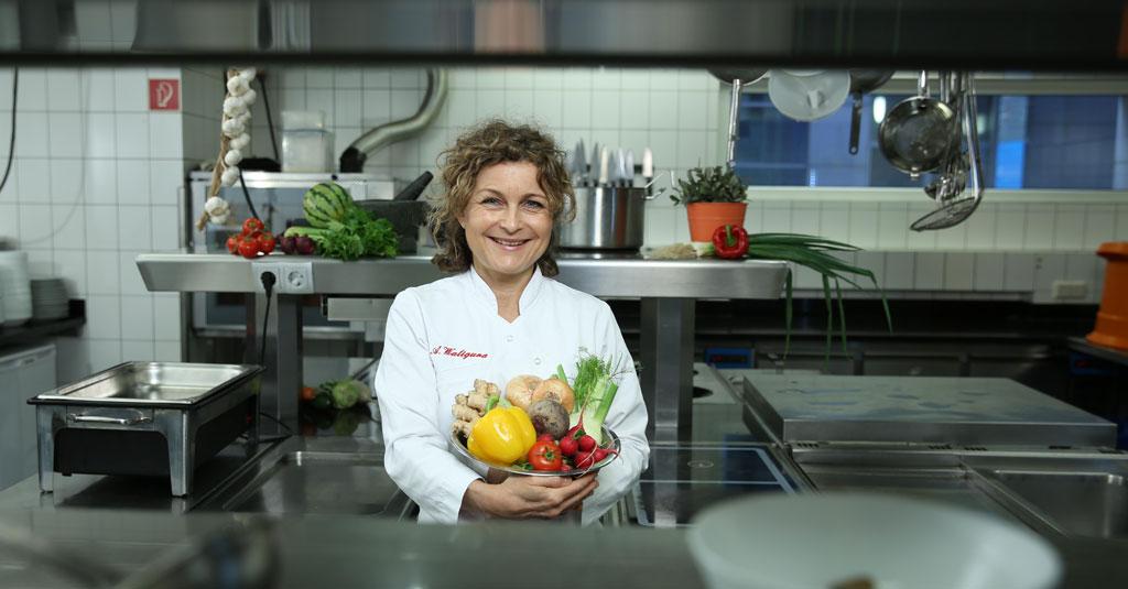 Köchin Astrid Waligura mit Gemüseschale in Küche