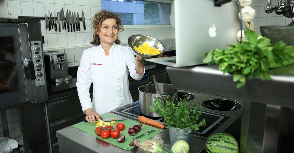 Köchin Astrid Waligura bei der Zubereitung von Gemüse in Küche bei der Videoaufnahme.