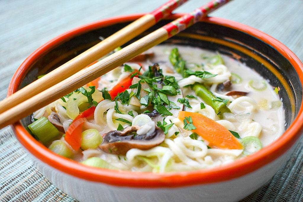 Thailändische Kokos-Champignonsuppe in Suppenschale mit Stäbchen